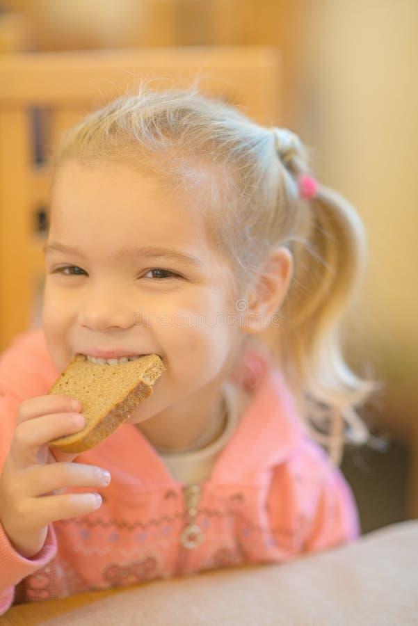 Mooi meisje het bijten brood. stock afbeelding