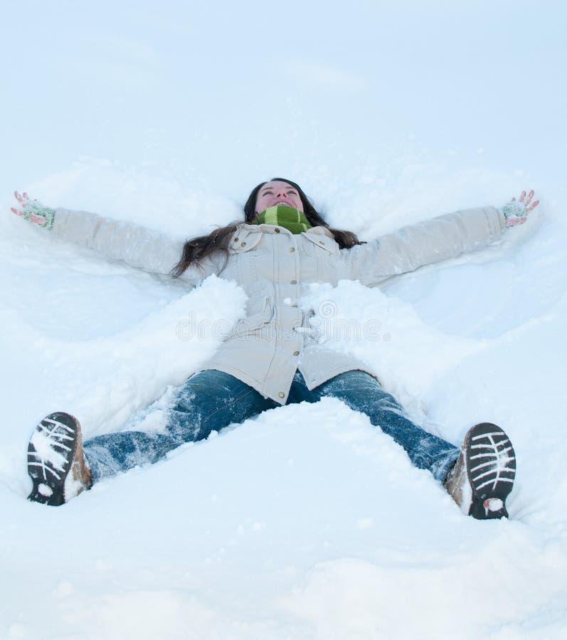 Mooi meisje in het groene liggen in sneeuw royalty-vrije stock afbeeldingen