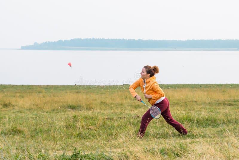 Mooi meisje in het heldere badminton van sportkledingsspelen op kust van meer royalty-vrije stock afbeelding