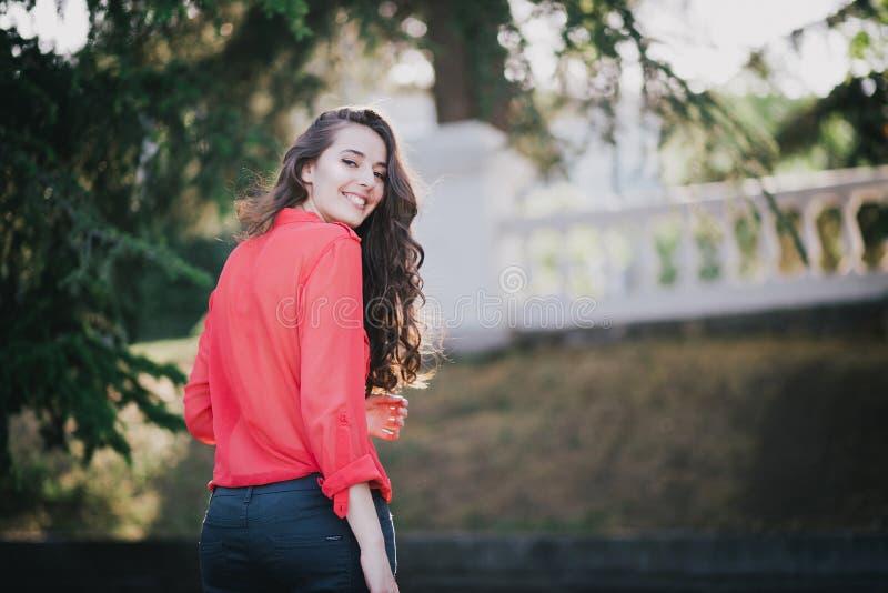Mooi meisje in het rode overhemd stellen op een straat royalty-vrije stock afbeeldingen