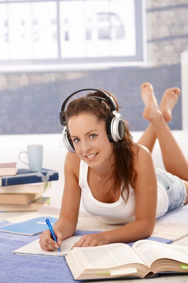 Mooi meisje het schrijven thuiswerk die op vloer leggen stock foto