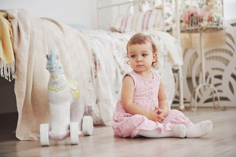 Mooi meisje het spelen speelgoed Blauw-eyed blonde Witte stoel Kinderen` s ruimte Gelukkig klein meisjesportret Kinderjaren royalty-vrije stock foto