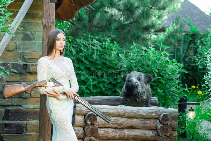 Mooi meisje in het witte kleding stellen met een de jachtgeweer en een gevulde beer op achtergrond stock afbeelding