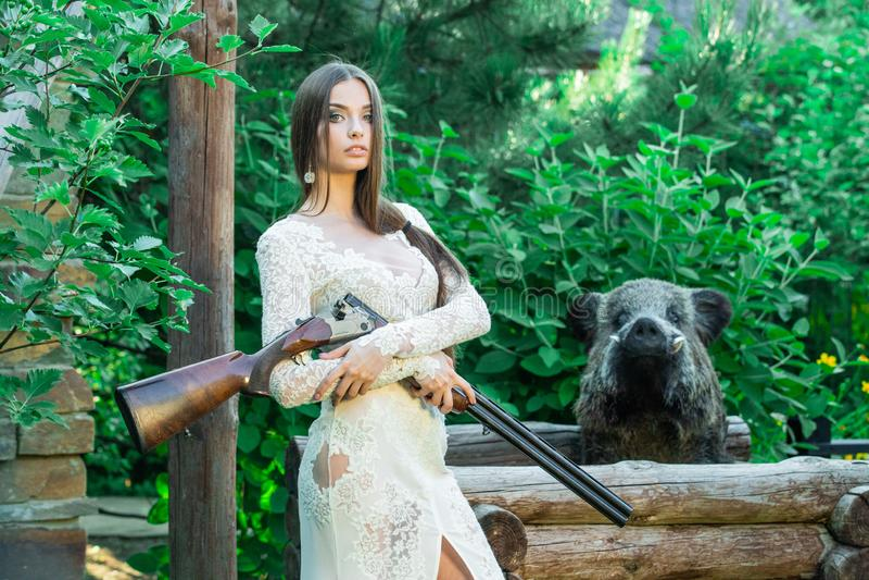 Mooi meisje in het witte kleding stellen met een de jachtgeweer en een gevulde beer op achtergrond stock afbeeldingen