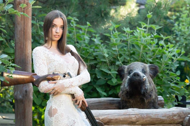 Mooi meisje in het witte kleding stellen met een de jachtgeweer stock foto
