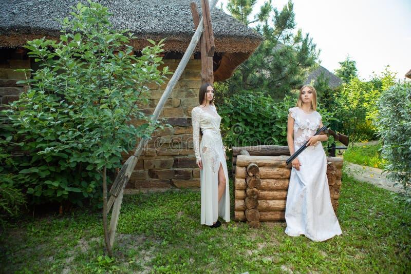 Mooi meisje in het witte kleding stellen met een de jachtgeweer royalty-vrije stock afbeelding