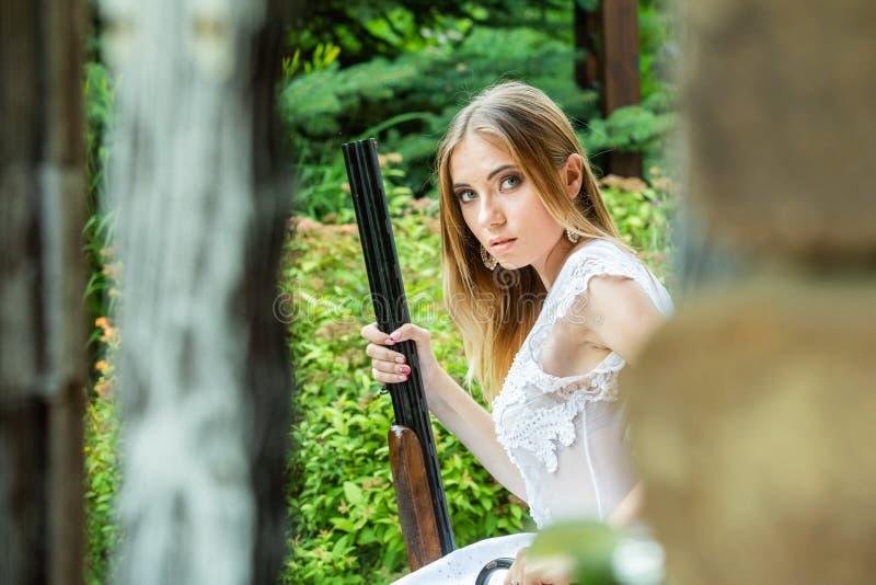 Mooi meisje in het witte kleding stellen met een de jachtgeweer royalty-vrije stock fotografie