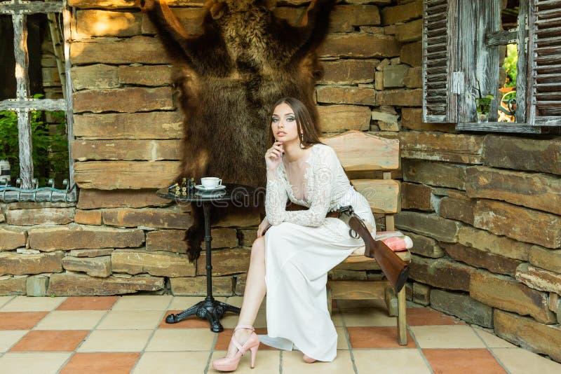 Mooi meisje in het witte kleding stellen met een de jachtgeweer op de achtergrond van een beerhuid stock fotografie