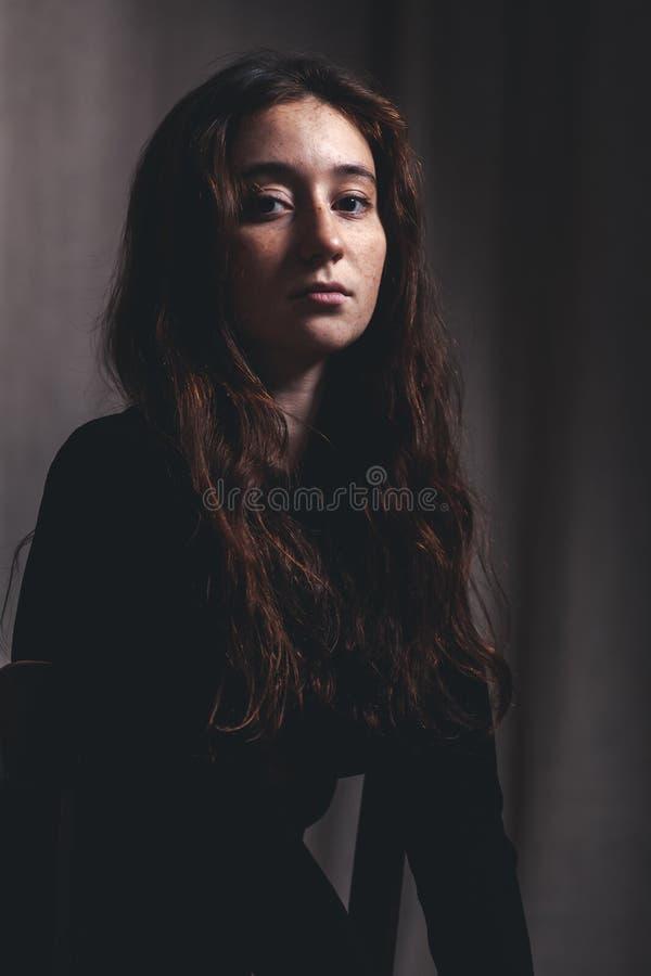 Mooi meisje 17-18 jaar oud met lange haar en sproeten, een ernstige blik in de camera, portret in donkere kleuren royalty-vrije stock foto