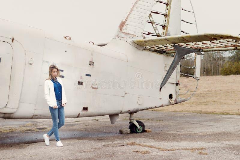 Mooi meisje in jeans en een wit jasje die zich dichtbij een oud vliegtuig op een bewolkte dag bevinden royalty-vrije stock foto's