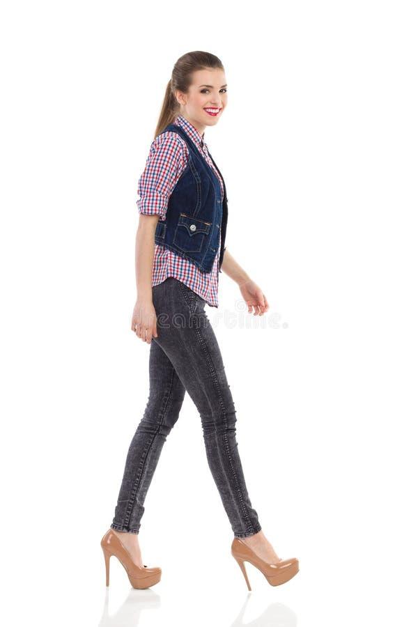 Mooi meisje in jeansvest het lopen stock fotografie