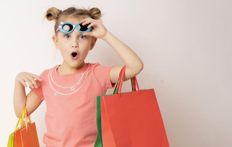 Mooi meisje kleding dragen en zonnebril die het winkelen zakken houden stock afbeeldingen