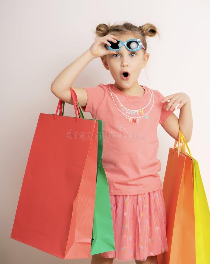 Mooi meisje kleding dragen en zonnebril die het winkelen zakken houden stock foto's