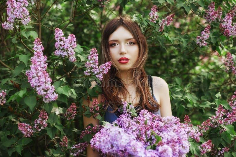 Mooi meisje in kleding het stellen dichtbij Bush van seringen op een de zomerdag, purpere bloemen in het Park De lenteportret van stock foto