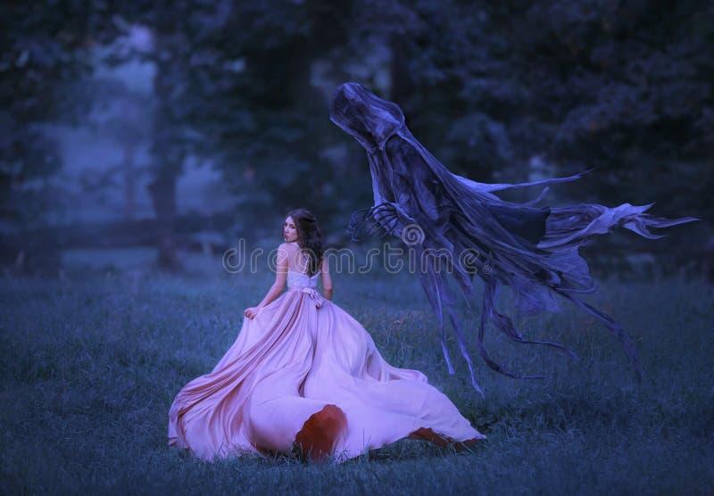 Mooi meisje in lang, roze, het fladderen kledingslooppas vanaf dood in de vorm van een donker demon dat uit hel kwam stock afbeeldingen