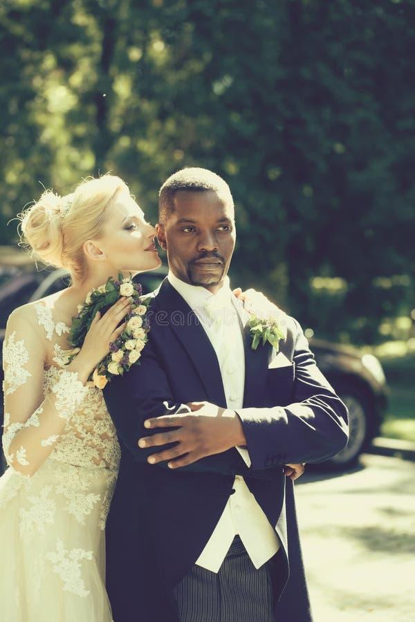 Mooi meisje of leuke bruid die knappe Afrikaanse Amerikaanse bruidegom koesteren stock foto's