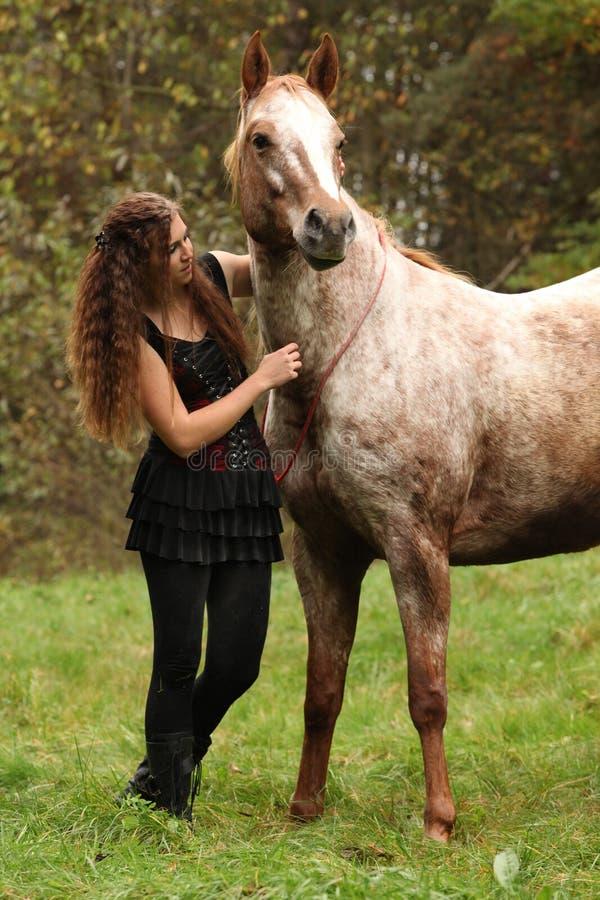 Mooi meisje met aardige kleding die zich naast aardig paard bevinden royalty-vrije stock fotografie