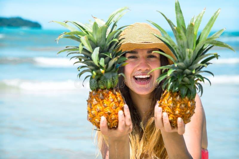 Mooi meisje met ananas op een exotisch strand, een gelukkige stemming en een mooie glimlach royalty-vrije stock foto's