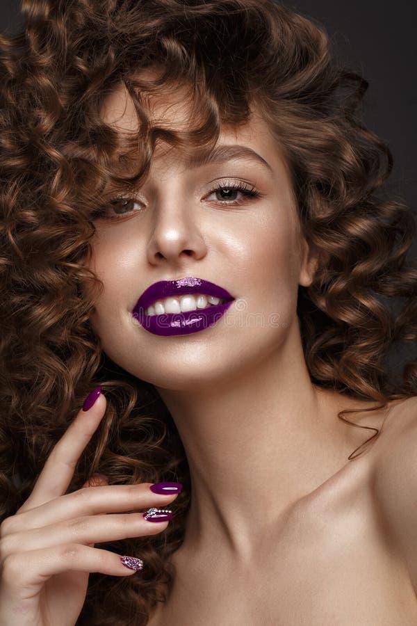 Mooi meisje met avondsamenstelling, purpere lippen, krullen en de spijkers van de ontwerpmanicure Het Gezicht van de schoonheid stock afbeeldingen