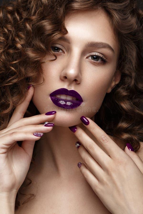 Mooi meisje met avondsamenstelling, purpere lippen, krullen en de spijkers van de ontwerpmanicure Het Gezicht van de schoonheid royalty-vrije stock foto