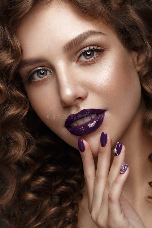 Mooi meisje met avondsamenstelling, purpere lippen, krullen en de spijkers van de ontwerpmanicure Het Gezicht van de schoonheid stock foto's