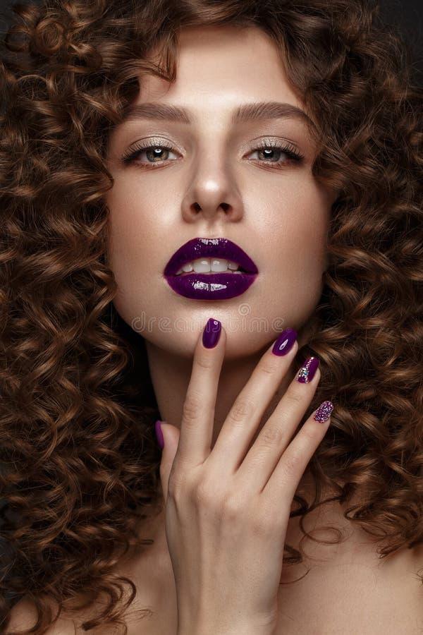 Mooi meisje met avondsamenstelling, purpere lippen, krullen en de spijkers van de ontwerpmanicure Het Gezicht van de schoonheid royalty-vrije stock fotografie