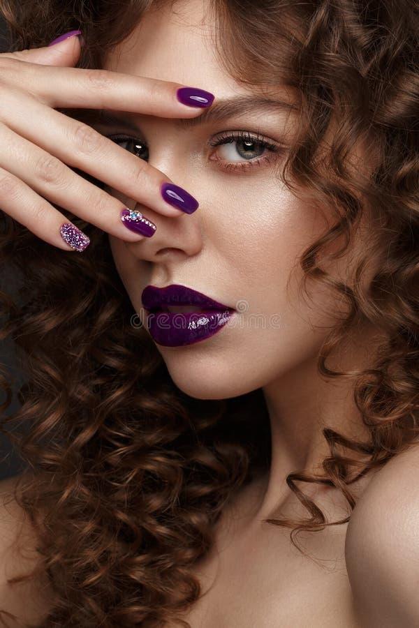 Mooi meisje met avondsamenstelling, purpere lippen, krullen en de spijkers van de ontwerpmanicure Het Gezicht van de schoonheid royalty-vrije stock afbeeldingen