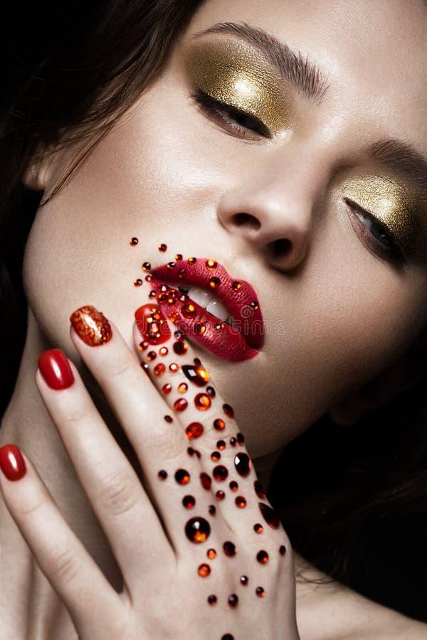 Mooi meisje met avondsamenstelling, rode lippen in bergkristallen en de spijkers van de ontwerpmanicure Het Gezicht van de schoon stock fotografie