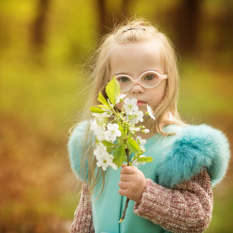 Mooi meisje met beneden de lentebloemen van de syndroomholding stock foto's