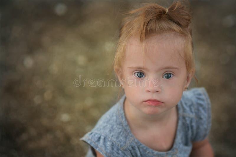 Mooi meisje met Benedensyndroom op het strand stock afbeelding