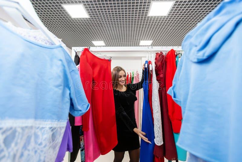 Mooi meisje met blauwe kleding dichtbij spiegel op ruimteachtergrond Gelukkige jonge vrouw die kleren in wandelgalerij of kleding stock afbeeldingen