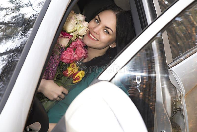 Mooi meisje met bloemen in de auto stock foto's
