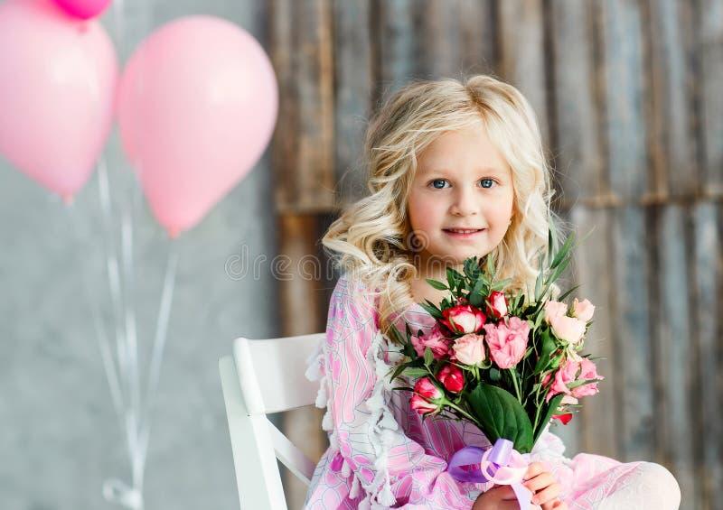 Mooi meisje met blond haar en een boeket van verse bloemen in een heldere studio Daglicht royalty-vrije stock afbeeldingen