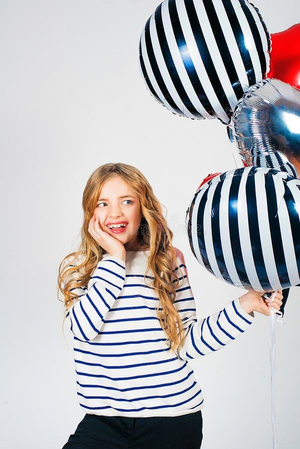 Mooi meisje met blond haar en heldere ballonsharten en giften voor de Dag van Valentine stock foto's