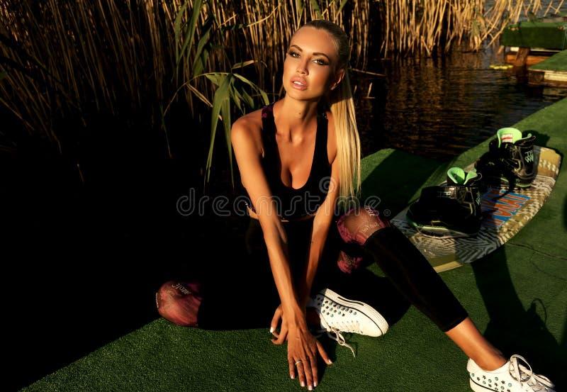Mooi meisje met blond haar in zwempak het stellen bij zonsondergang beac stock foto