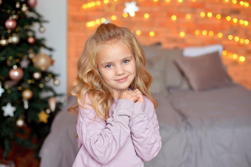 Mooi meisje met blonde krullen in verwachting van giften in de achtergrondkerstmislichten en het bed Nieuw jaar en royalty-vrije stock foto's