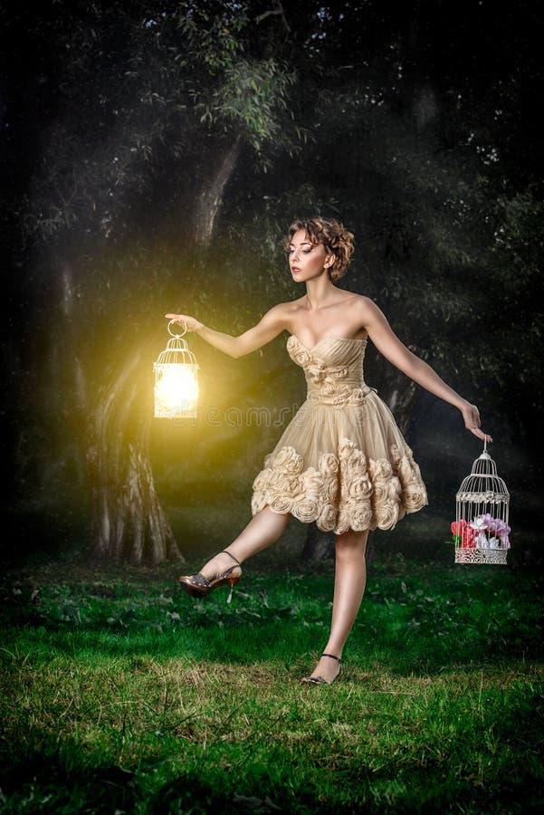 Mooi meisje met bruin krullend haar en lange benen in prachtige kleding in foto van de fairytale de boskunst royalty-vrije stock afbeeldingen
