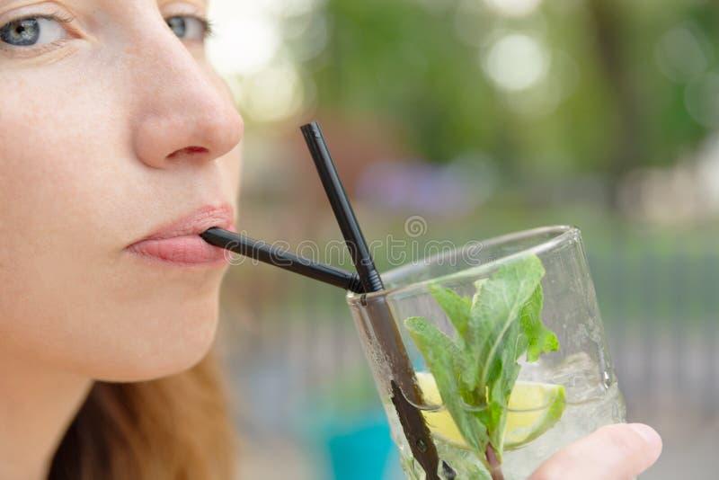 Mooi meisje met de drank van de mojitococktail in openluchtrestaurant stock foto