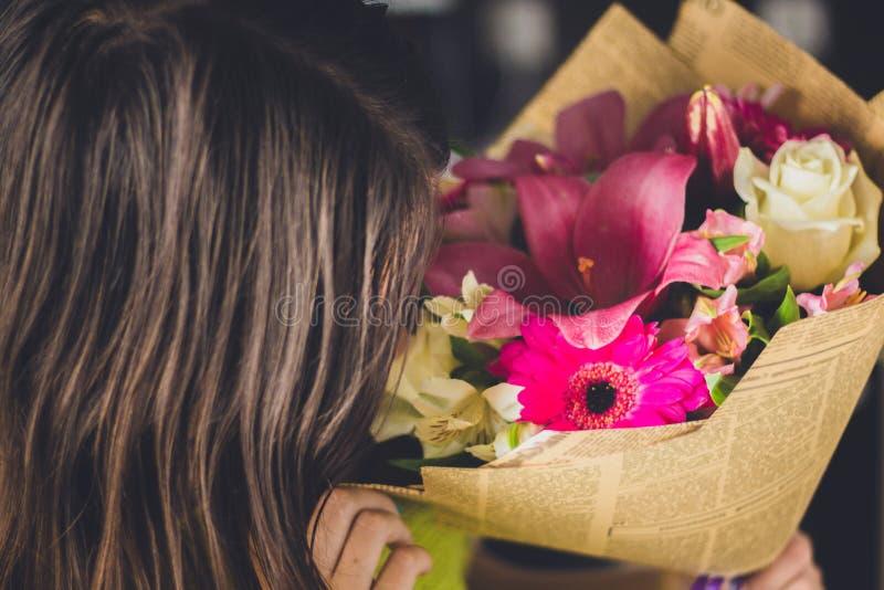 Mooi meisje met donker haar met een boeket van bloemen van een lelie, een gerbera, witte rozen en een alstroemeria op een donkere royalty-vrije stock foto's