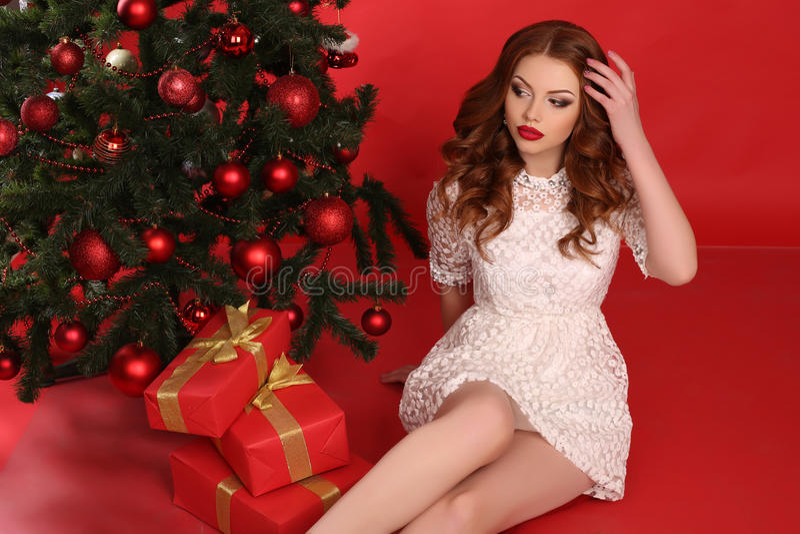 Mooi meisje met donker haar in elegante kleding met grote aanwezige Kerstmis stock fotografie