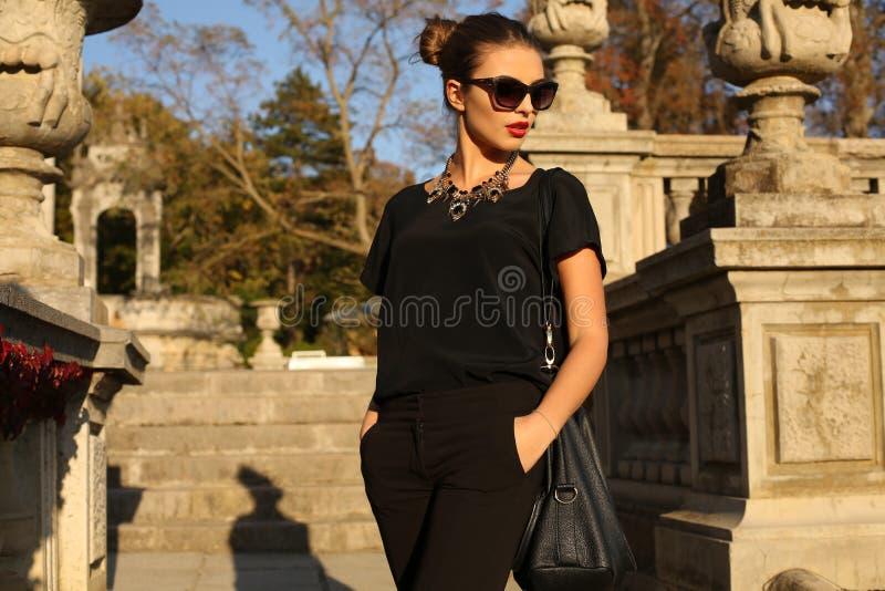 Mooi meisje met donker haar in elegante kleren die in de herfstpark stellen royalty-vrije stock afbeelding