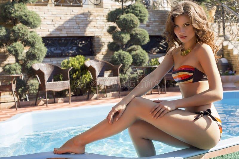 Mooi meisje met donker haar in kleurrijke bikini stock afbeeldingen