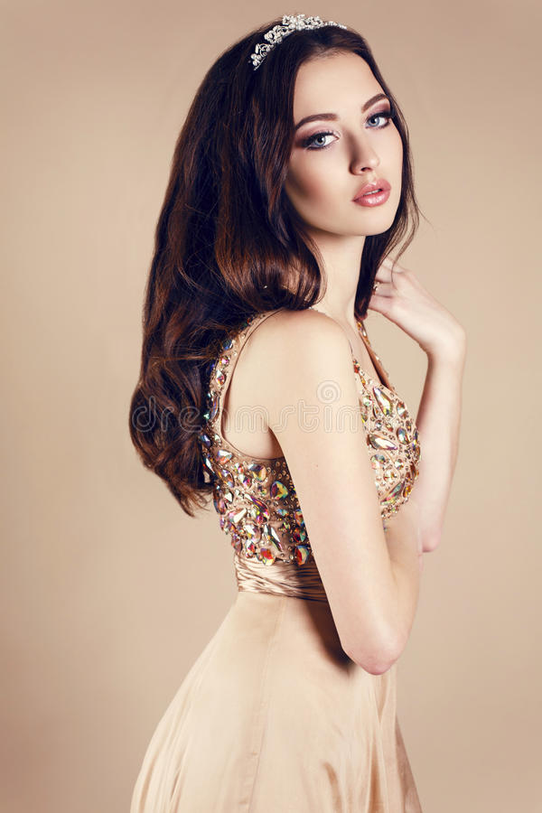 Mooi meisje met donker haar in luxueuze lovertjekleding en kroon royalty-vrije stock foto