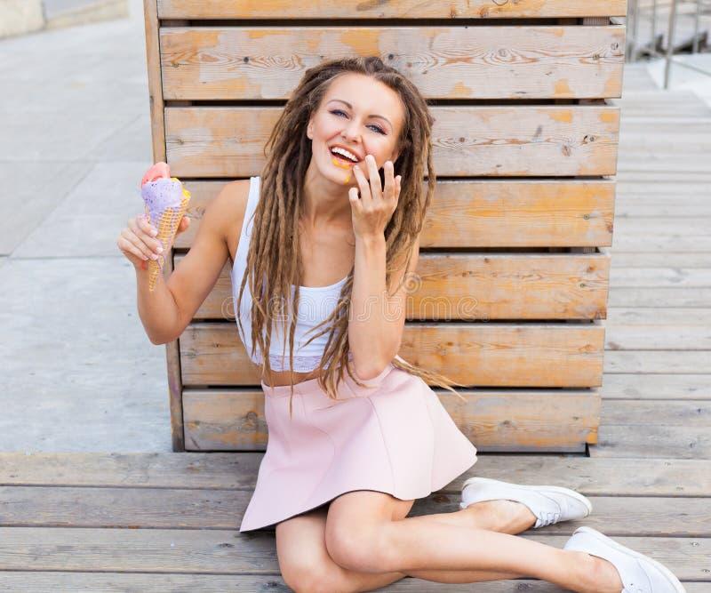 Mooi meisje met dreadlocks in roze rokzitting op de veranda en het eten van kleurrijk ijshoorntje op een warme de zomeravond stock foto's