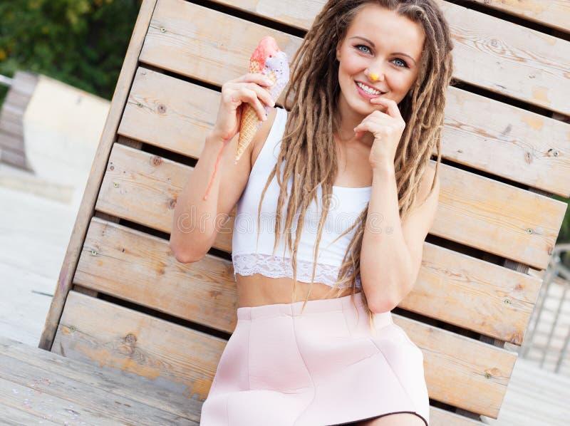 Mooi meisje met dreadlocks in roze rokzitting op de veranda en het eten van kleurrijk ijshoorntje op een warme de zomeravond C royalty-vrije stock afbeeldingen