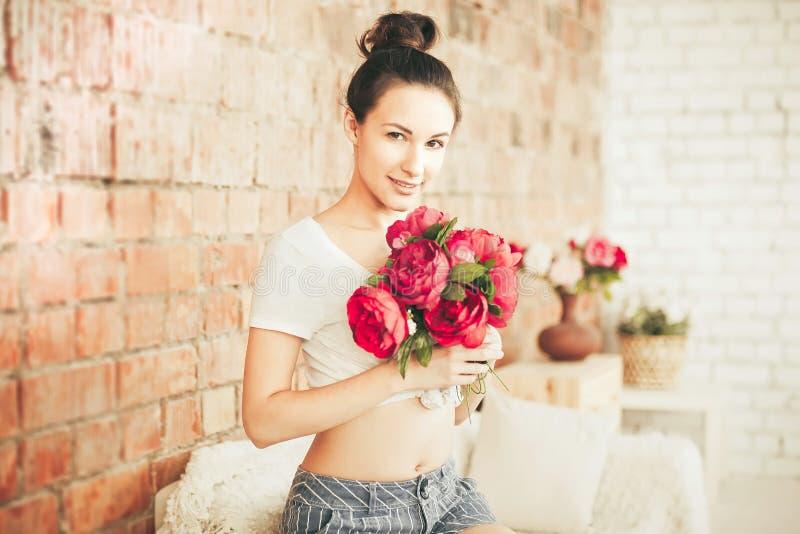 Mooi meisje met een boeket van rode bloemen stock fotografie