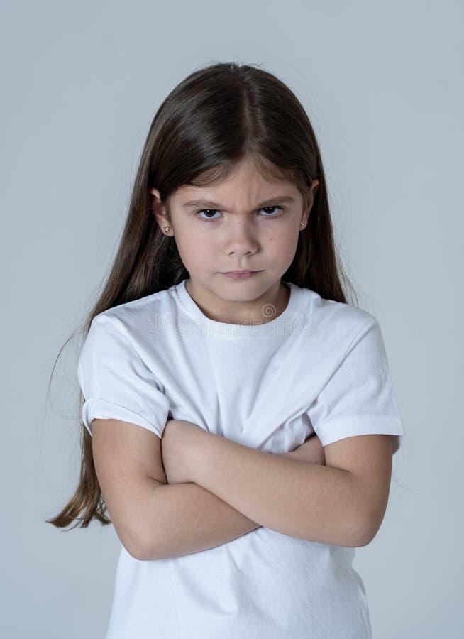 Mooi meisje met een boze gelaatsuitdrukking die gek de camera bekijken Kinderenemoties stock afbeeldingen