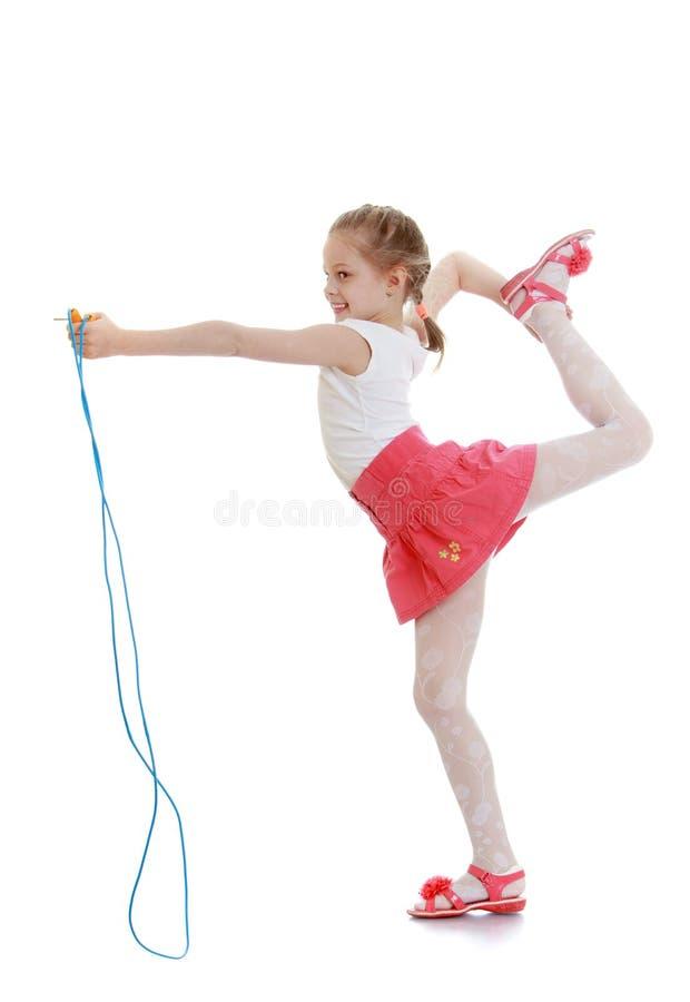 Mooi meisje met een geel touwtjespringen in uw royalty-vrije stock afbeelding