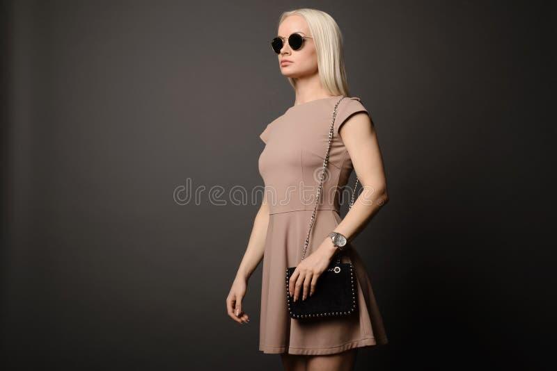 Mooi meisje met een handtas en zonnebril stock afbeeldingen