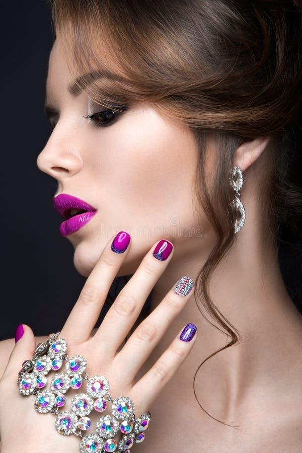 Mooi meisje met een heldere avondsamenstelling en een purpere manicure met bergkristallen Spijkerontwerp Het Gezicht van de schoo stock foto